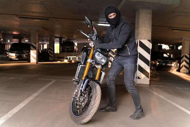 Zbliżenie na człowieka przygotowującego się do kradzieży motocykla