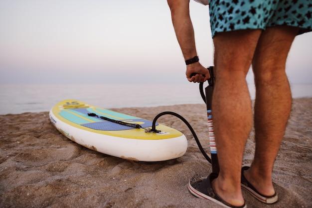 Zbliżenie na człowieka przygotowuje się do wiosłowania na plaży pompującej deskę sup