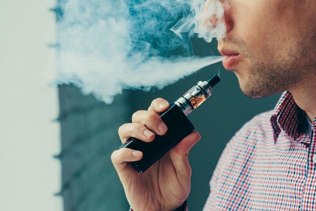 Zbliżenie na człowieka wydychającego parę z papierosa elektronicznego