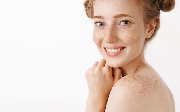 Zbliżenie na delikatną i kobiecą, przystojną imbirową kobietę stojącą nago w profilu, obracającą się ze szczęśliwym uroczym uśmiechem, ciesząc się kąpielą i relaksując się podczas zabiegu kosmetycznego