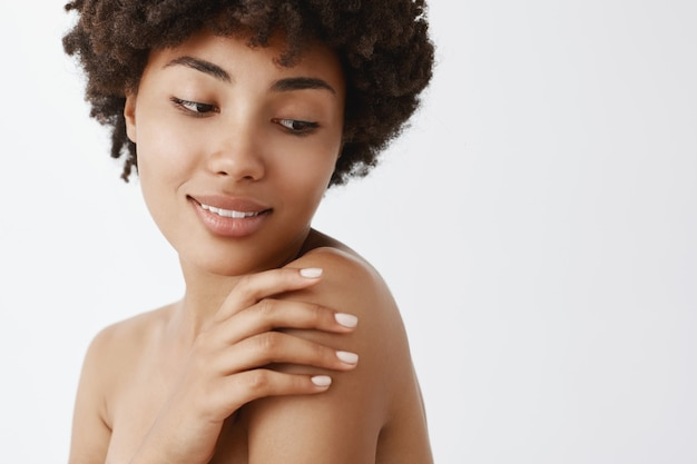 Zbliżenie na delikatną kobiecą afroamerykańską kobietę z kręconymi włosami, skręcającą w prawo, dotykającą ramienia i uśmiechającą się z miękkim rozmarzonym wyrazem twarzy
