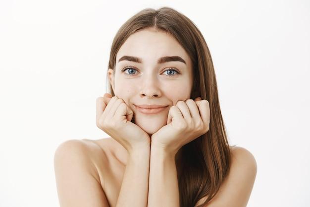 Zbliżenie na delikatną kobiecą, młodą brunetkę pozującą nagą, opartą na dłoniach twarz i uśmiechniętym spojrzeniem oczarowanym podziwem, uczuciem marzycielskim