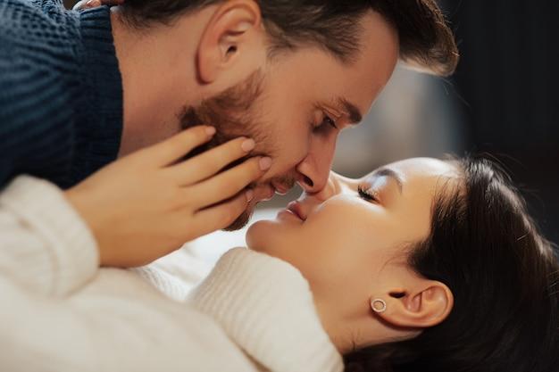 Zbliżenie na delikatną kobietę z zamkniętymi oczami i brodaty mężczyzna spędzają razem czas.