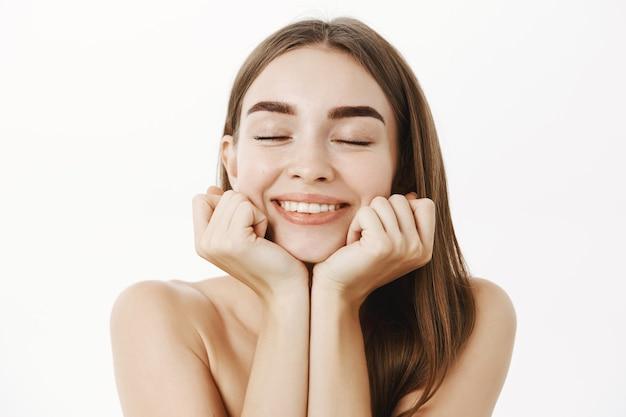 Zbliżenie na delikatną rozmarzoną i kobiecą ładną kobietę z brązowymi włosami, opartą na dłoniach z zamkniętymi oczami i słodkim, zachwyconym uśmiechem przypominającym lub wyobrażającym sobie miły moment