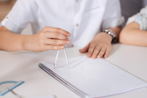Zbliżenie na delikatne, schludne dłonie chłopca siedzącego przy stole, trzymającego kompas i wpisującego kółka