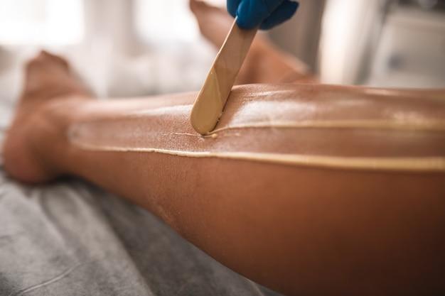 Zbliżenie na depilację kosmetyczki gorącym woskiem kobiecej nogi w spa