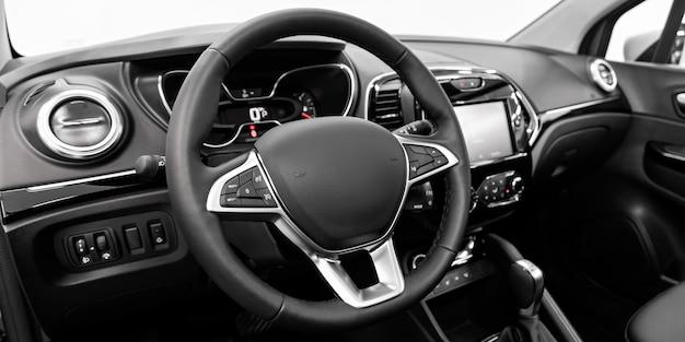 Zbliżenie na deskę rozdzielczą, odtwarzacz, kierownicę, rączkę gazu, przyciski, siedzenia.