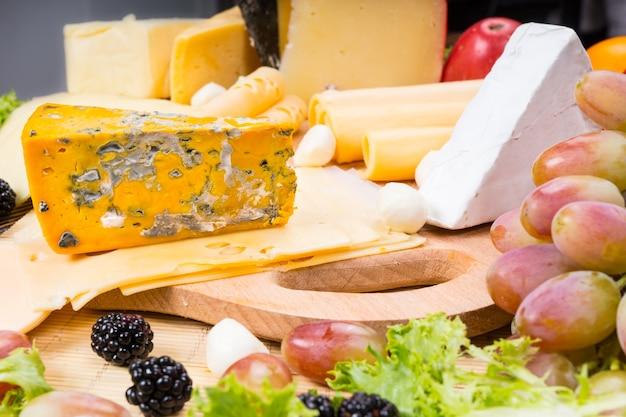 Zbliżenie na deskę serów dla smakoszy z obfitością różnych serów i przyozdobionymi świeżymi owocami, podawane na drewnianej desce do krojenia