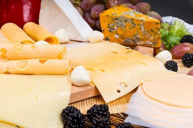 Zbliżenie na deskę serów dla smakoszy z różnymi serami i przyozdobionymi świeżymi owocami - smaczna i obfita przystawka do serów