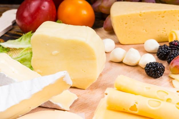 Zbliżenie na deskę serów dla smakoszy z różnymi serami i przyozdobionymi świeżymi owocami - szczegół apetycznej deski serów