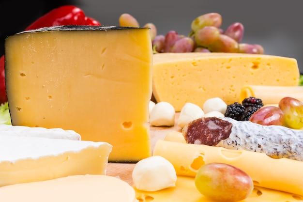 Zbliżenie na deskę serów dla smakoszy z różnymi serami, wędlinami i przyozdobionymi owocami - szczegóły apetycznej deski serów