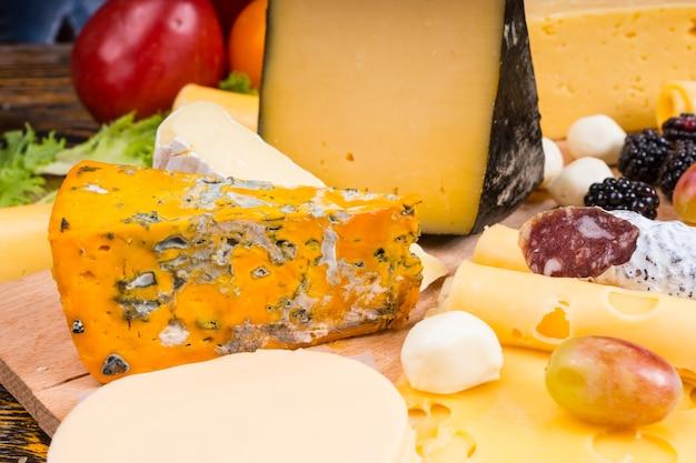 Zbliżenie na deskę serów dla smakoszy z różnymi serami, wędlinami i przyozdobionymi świeżymi owocami