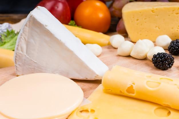 Zbliżenie na deskę z serami dla smakoszy z naciskiem na klin brie otoczony różnymi serami i przyozdobionymi świeżymi owocami