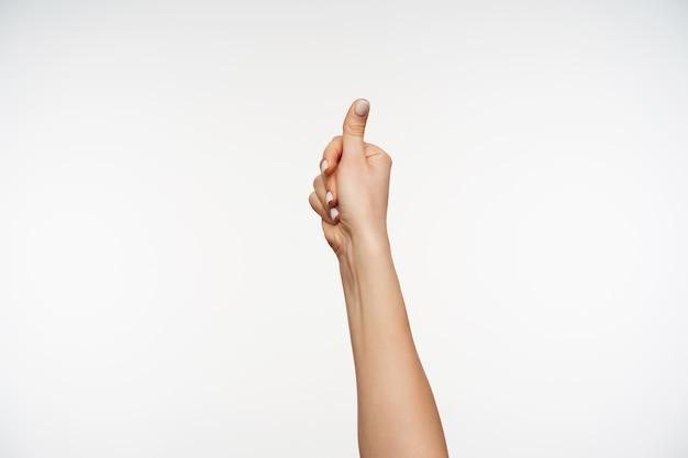 Zbliżenie na dłoń młodej kobiety o jasnej karnacji, która jest podnoszona podczas kciuka