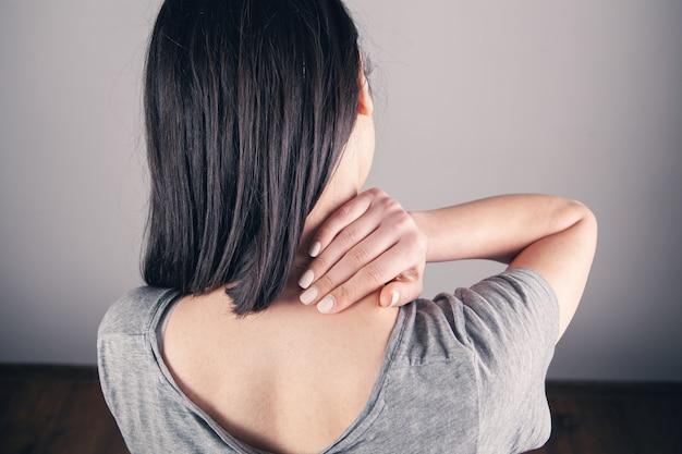 Zbliżenie na dłoni womans masuje jej szyję. szyja dziewczyny boli