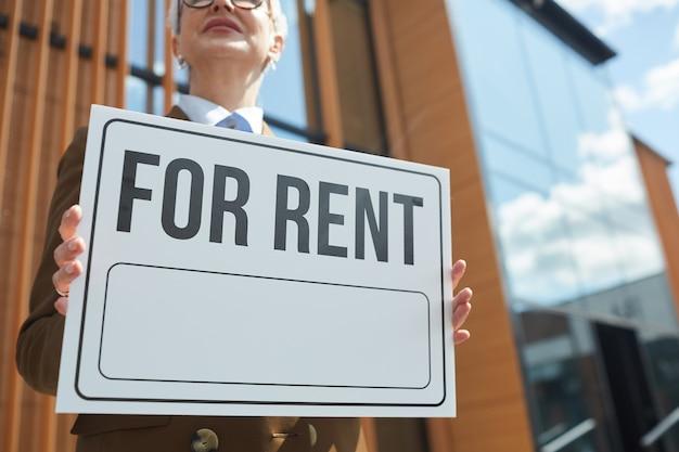 Zbliżenie na dojrzałą bizneswoman trzyma afisz, pracuje jako pośrednik w handlu nieruchomościami i sugeruje biura do wynajęcia