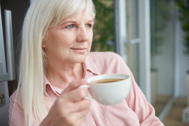 Zbliżenie na dojrzałą kobietę, ciesząc się dobrą kawą na balkonie