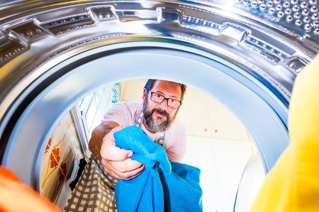 Zbliżenie na dojrzałego mężczyznę, sprzątanie i pranie ubrań w domu w pralce w kwarantannie lub blokadzie - mężczyzna pomagający w pracy domowej