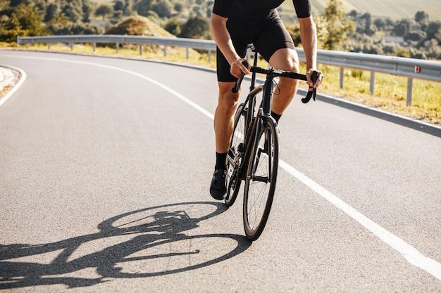 Zbliżenie na dojrzały mężczyzna z silnym ciałem na sobie odzież rowerową i trampki, jazda na rowerze na wsi.