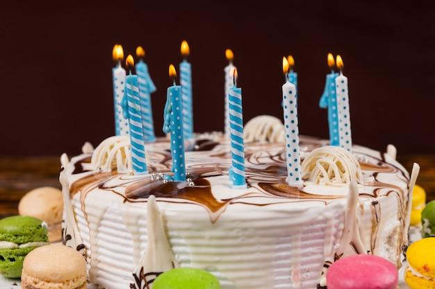 Zbliżenie na domowy tort urodzinowy z dużą ilością płonących świec w pobliżu różnych kolorowych makaroników, na drewnianym biurku