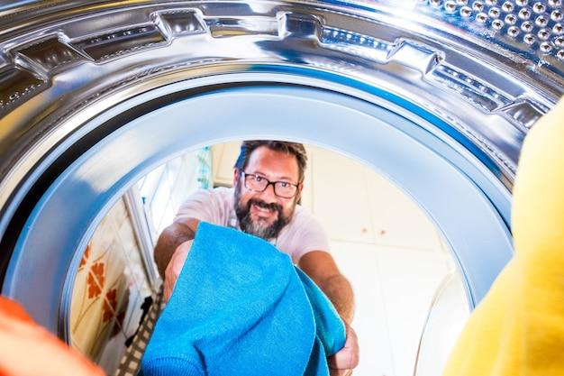 Zbliżenie na dorosłego mężczyznę sprzątającego i wkładającego ubrania do pralki - mężczyzna robi prace domowe
