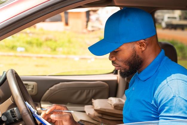 Zbliżenie na dostawcę z dokumentami w samochodzie