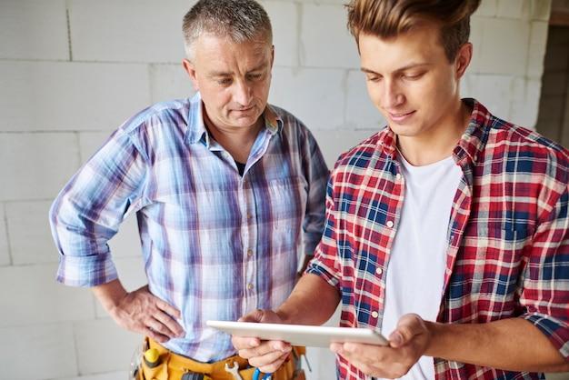 Zbliżenie na doświadczonego stolarza i jego młodszego pracownika