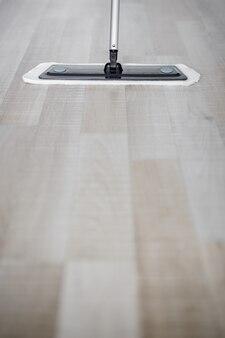 Zbliżenie na drewnianą podłogę z mopem z mikrofibry i przestrzenią do kopiowania