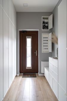 Zbliżenie na drewniane drzwi na korytarzu w stylu minimalizmu.