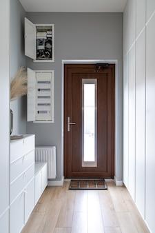 Zbliżenie na drewniane drzwi w przedpokoju w stylu minimalizmu.