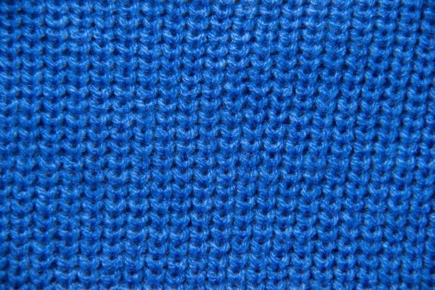 Zbliżenie na drutach. zbliżenie kolorowe dzianiny wełniane. niebieskie tło