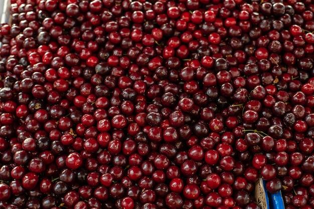 Zbliżenie na dużą kolekcję świeżych czerwonych wiśni. dojrzałe wiśnie w tle