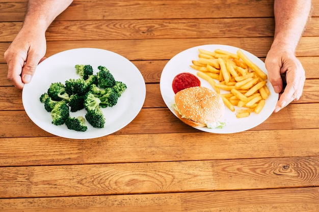 Zbliżenie na dwa talerze na drewnianym stole - mężczyzna lub kobieta wybierając między brokułami lub fast foodami, takimi jak hamburger ze smażonymi frytkami - dieta styl życia i zdrowa koncepcja
