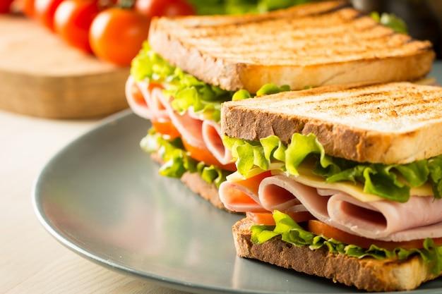Zbliżenie na dwie kanapki z boczkiem, salami, szynką prosciutto i świeżymi warzywami na rustykalnej drewnianej desce do krojenia. koncepcja kanapki klubowej.