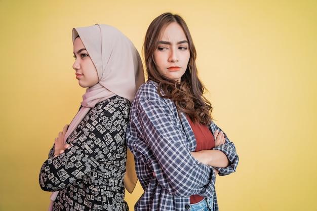 Zbliżenie na dwie smutne dziewczyny stojące plecami do siebie i skrzyżowane ręce