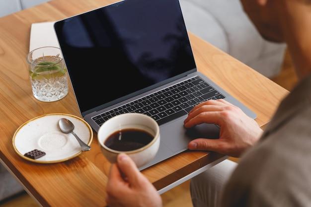 Zbliżenie na dżentelmena pijącego kawę i pracującego nad nowoczesnym notebookiem w kawiarni