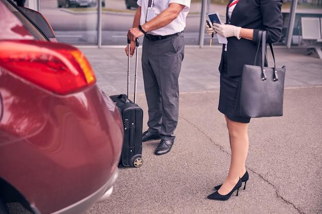 Zbliżenie na dżentelmena trzymającego walizkę podróżną, stojącego obok bizneswoman w sterylnych rękawiczkach