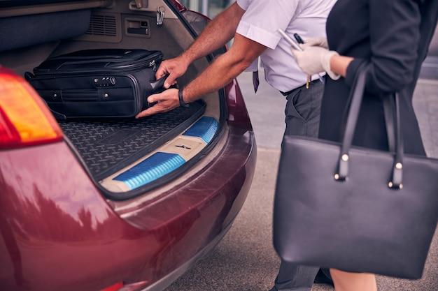 Zbliżenie na dżentelmena umieszczającego walizkę podróżną w bagażniku, podczas gdy bizneswoman w sterylnych rękawiczkach stoi obok niego