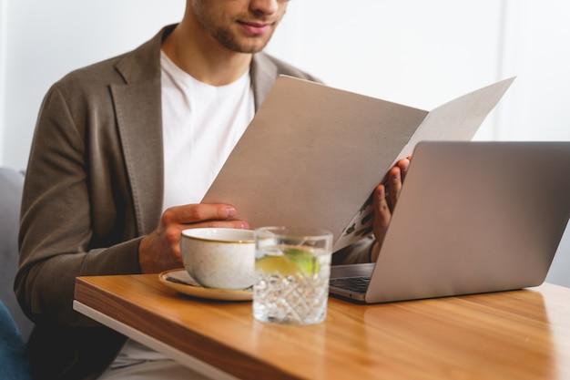 Zbliżenie na dżentelmena wybierającego jedzenie siedząc przy stoliku kawiarnianym z nowoczesnym notatnikiem i filiżanką kawy