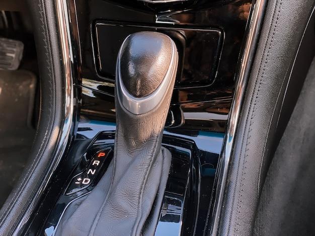 Zbliżenie na dźwignię zmiany biegów w samochodzie. zdjęcie wnętrza samochodu w kolorze czarnym.