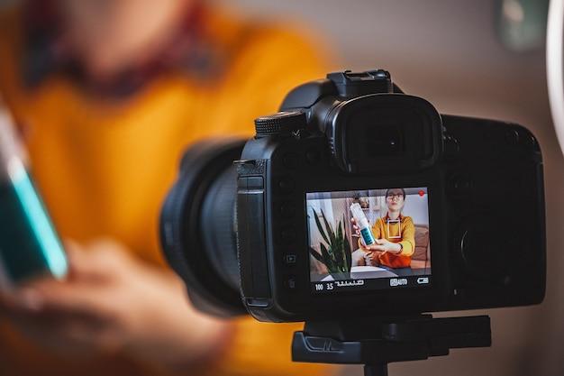 Zbliżenie na ekran aparatu, blogerka kosmetyczna robi recenzję wideo