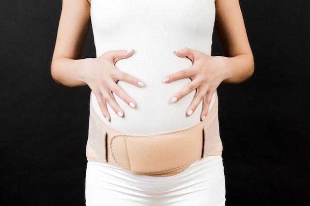 Zbliżenie na elastyczną opaskę macierzyńską ubraną na kobietę w ciąży, aby zmniejszyć ból pleców