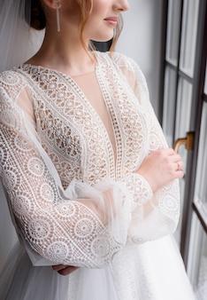 Zbliżenie na elegancką białą sukienkę z makramy noszonej przez pannę młodą stojącą przy oknie