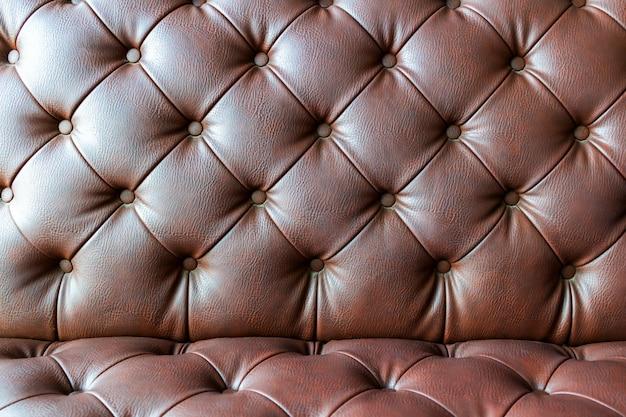 Zbliżenie na elegancką brązową skórzaną sofę w stylu vintage chesterfield z siedziskiem