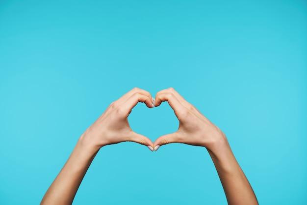 Zbliżenie na eleganckie podniesione ręce, tworząc serce z palcami na białym tle