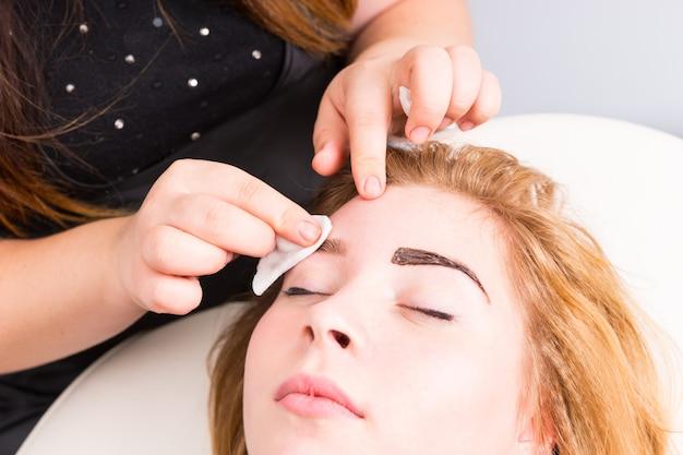 Zbliżenie na estetykę czyszczenie nadmiaru barwnika z brwi blond klientki leżącej na krześle w białym spa, za pomocą wacika kosmetycznego