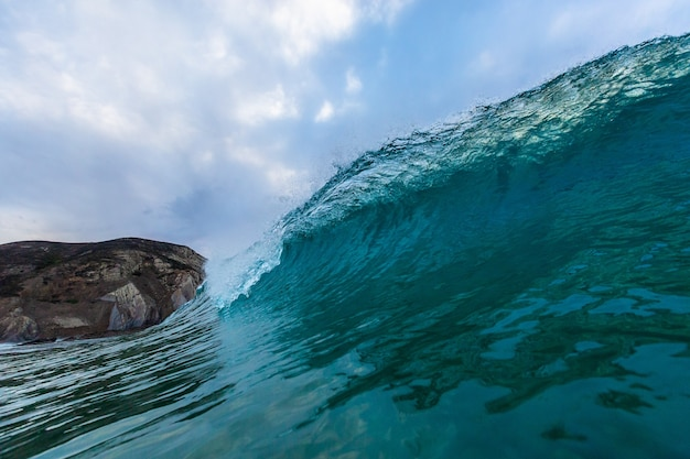 Zbliżenie na falę morską ze skałami pod pochmurnym niebem w algarve, portugalia