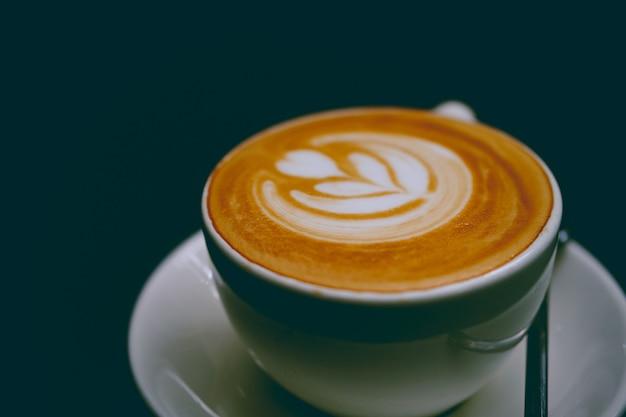 Zbliżenie na filiżankę pysznej latte na spodku