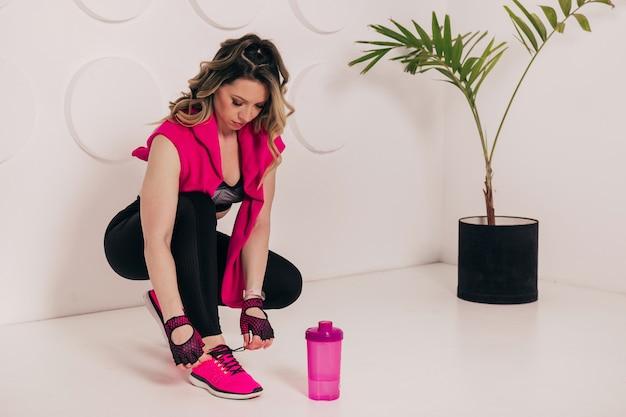 Zbliżenie na fitness młoda kobieta siedzi na podłodze siłowni i zakłada jej różowe trampki.