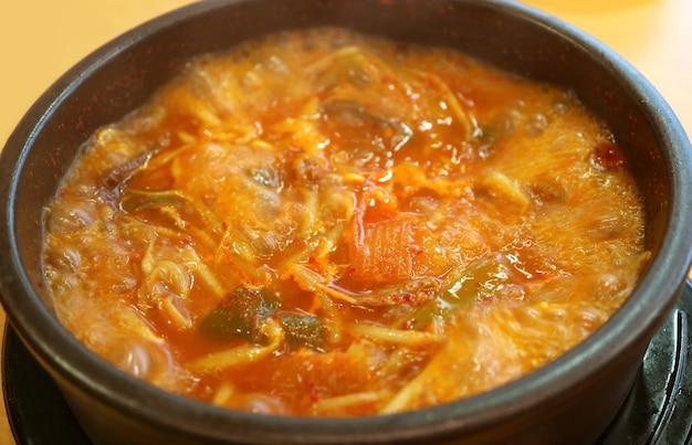 Zbliżenie na garnek koreańskiego gorącego i pikantnego gulaszu kimchi lub kimchi jjigae